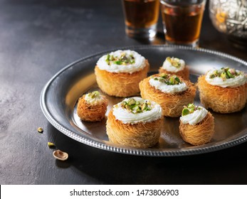 Kataifi, kadayif, kunafa, baklava pastry nests cookies with pistachios with tea. Cooking sweets turkish, or arabic traditional ramadan pastry dessert on a dark background.