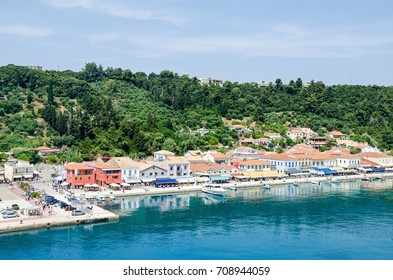 Katakolo, Greece - June 6, 2017: Waterfront and promenade of Katakolo, a small seaside town, with its natural harbour, hills with forests, many tourists and some boats