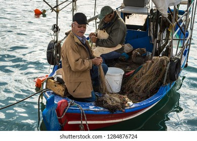 Katakolon, Greece - October 31, 2017: Local fishermen soarting out his nets. Fresh sea food. Catch of the day. Greek local fishermen. Working in the docks on the boat. Aegean lifestyle. Island life.