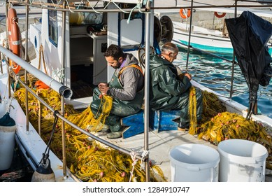 Katakolon, Greece - October 31, 2017: Greek fishermen collect the fish in nets after fishing in his boat. Fishing in wooden traditional boats remains an important part of the local economy in Greece.