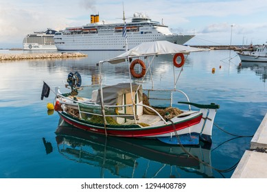 Katakolon, Greece - October 31, 2017: Fishing boats and Costa neoClassica Cruise Ship moored in the port of the Katakolon, Greece. Katakolon is a port town in western Greece, facing the Ionian Sea.