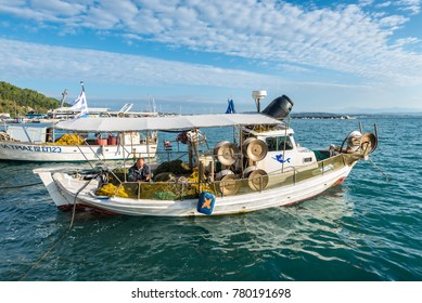 Katakolon, Greece - October 31, 2017: Traditional colorful wooden fishing boats in harbor of the Katakolon (Olimpia), Greece. Greek fisherman collect the fish in nets after fishing in his boat.