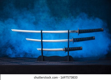 Katana, wakizashi and tanto on a stand with exposed blades, blue smoke behind