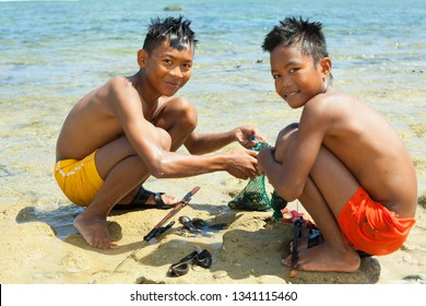 Katanduwanes, Philippines - March 1, 2019: two children on the shore of the Pacific Ocean with fish caught