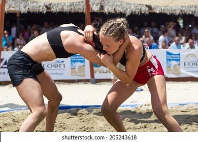 KATERINI, GREECE- JULY 6, 2014: Two female athletes wrestle on sand during the First World Championship Beach Wrestling in 2014 in Katerini, Greece.
