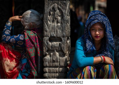 Kathmandu, Kathmandu/Nepal - Jan 08, 2020: Nepali Girl wear blue suit head cover with blue scarf sitting with an old lady at day time with harsh light