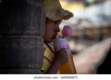 Kathmandu, Kathmandu/Nepal - Jan 08, 2020: A Small Nepali Girl wearing Yellow suit and hat, drinking orange juice from feeder