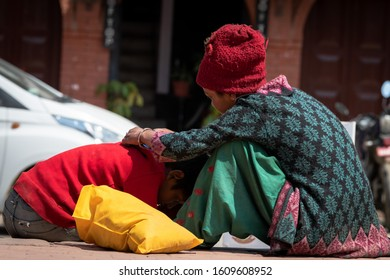 Kathmandu, Kathmandu/Nepal - Jan 08, 2020: A Nepali family sitting beside and mother taking out lice from head of kid at day time