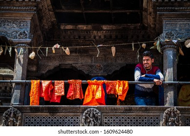 Kathmandu, Kathmandu/Nepal - Jan 08, 2020: A Nepali Man Standing in Balcony of house and Orange cloths are tied beside him.