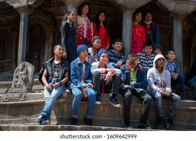 Kathmandu, Kathmandu/Nepal - Jan 08, 2020: Nepali School kids and a kid is holding a olympus camera sitting in middle