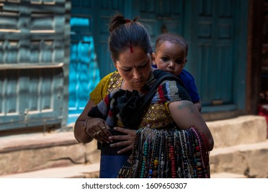 Kathmandu, Kathmandu/Nepal - Jan 08, 2020: A Nepali Mother carrying kid on the back