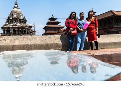 Kathmandu, Kathmandu/Nepal - Jan 08, 2020: A Nepali Family Standing in front of Bhaktapur Temple and reflection in the ground