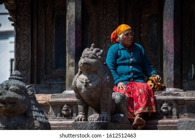 Kathmandu, Kathmandu/Nepal - Jan 08, 2020: An old Nepali Lady wearing blue shirt sitting in front of statue