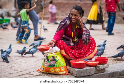 Kathmandu, Nepal - 06 October 2017: Woman in traditional clothes sells corn seeds on Nepalese street market, Nepal