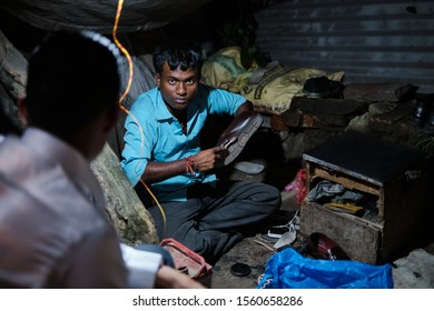 Kathmandu, Nepal - 23 October 2019: A Nepalese shoeshiner polishing shoes for his customers during night time at his shop in a street in Kathmandu, Nepal