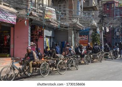 Kathmandu, Nepal - 7 January 2020:   rickshaw drivers waiting for their customers on the old center of Kathmandu in Nepal