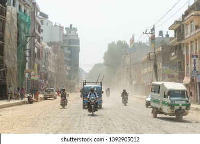 KATHMANDU, NEPAL - 9 MAY, 2019: Traffic on Boudha Road put dust in the air as the road is not blacktopped. It is on ongoing issue for the area's residents.