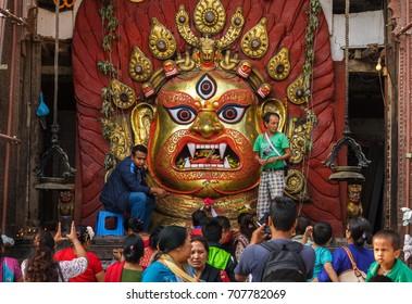 KATHMANDU, NEPAL - 9/26/2015: Devotees make offerings to Bhairav at Durbar Square during the Indra Jatra festival in Kathmandu, Nepal.