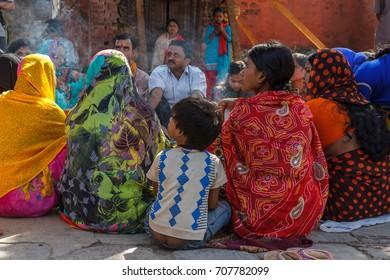 KATHMANDU, NEPAL - 9/26/2015: Hindu men and women in traditional sari sit together at Durbar Square in Kathmandu, Nepal.