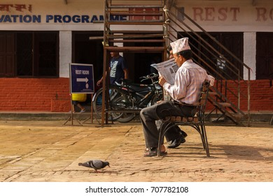 KATHMANDU, NEPAL - 9/26/2015: A Nepalese man reads a newspaper on a bench near Durbar Square in Kathmandu, Nepal.