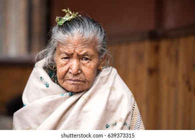 Kathmandu, Nepal - Apr 15, 2016: Elderly lady in traditional Nepalese clothing watching a passing ceremony procession.