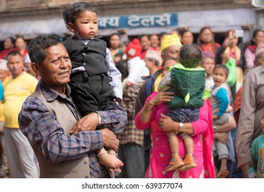 Kathmandu, Nepal - Apr 15, 2016: Father and his child watching passing ceremony procession.