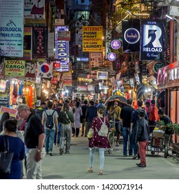 Kathmandu / Nepal - April 12 2019: A street view in the capital at night with a huge crowd on a small road in the tourist district of Thamel.