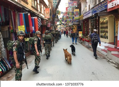 Kathmandu / Nepal - April 16 2019: A group of soldiers walking down the street in the tourist district Thamel in the capital.