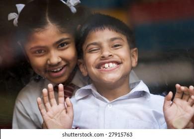 KATHMANDU, NEPAL - APRIL 17, 2008: Portrait of hindu children in school uniform are behind the glass.