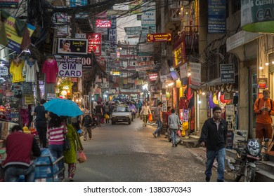 Kathmandu / Nepal - April 21 2019: A busy street in the tourist district Thamel on a rainy evening in the capital