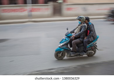 Kathmandu / Nepal - April 23 2019: Speeding motorcycle with motion blur going through traffic in the capital