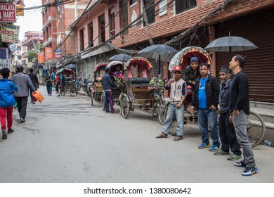 Kathmandu / Nepal - April 23 2019: Bicycle rickshaw drivers waiting for customers on a road on a cloudy day in the capital