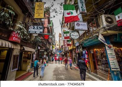 Kathmandu / Nepal | April 25 2017: Unidentified people walking through the colorful streets of Thamel neighborhood in Kathmandu, Nepal