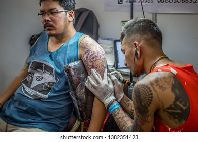 Kathmandu, Nepal - April 27 2019: A man getting a tattoo at a booth at the annual tattoo convention in the capital