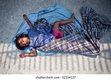 KATHMANDU, NEPAL - APRIL 6, 2010: A little boy sleeping on the street.