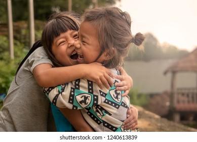 Kathmandu / Nepal - August 10 2018: Three happy kids hugging in the mountains of Nepal outside Kathmandu