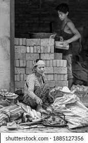 KATHMANDU, NEPAL - AUGUST 14, 2018: Unidentified nepalese woman cooking corn on the cob and unidentified nepalese man building a wall with bricks in the streets of Kathmandu, Nepal