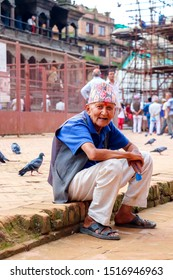 Kathmandu, Nepal - August 22 2019: An old Nepali man with happy face looking at the camera while siting at Patand Durbar Square