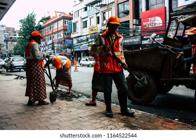 Kathmandu Nepal August 26, 2018 View of unknowns Nepali worker cleaning the street at Thamel district in Kathmandu in the afternoon