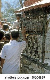 KATHMANDU NEPAL - CIRCA OCTOBER 1979 : Worshipers spin the prayer wheels in the Buddhist temple on Sywambunath circa October 1979 in Kathmandu, Nepal.