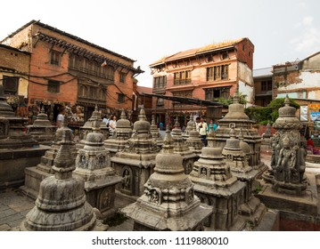 Kathmandu, Nepal - Circa September 2017 - A perspective shot of Swayambhunath stupas and unidentified tourists and visitors  in Monkey Temple with face brick building in the background