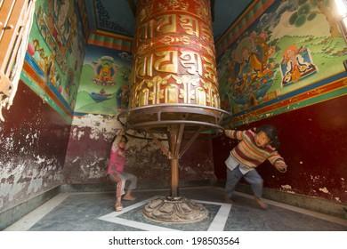 KATHMANDU, NEPAL - DEC 23, 2013: Unidentified children have fun with spinning Big Tibetan Buddhist prayer wheel at Boudhanath Stupa.