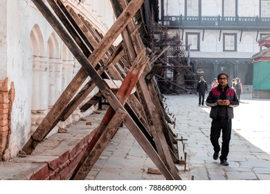 KATHMANDU, NEPAL - December 15, 2017 : Unknown man walking beside the building that use woods to keep the building not collapse from the earthquake in Kathmandu Dubar Square.
