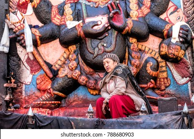 KATHMANDU, NEPAL - December 15, 2017 : Unidentified Nepali Woman is sitting in front of the sculpture at the temple in Kathmandu Dubar Square
