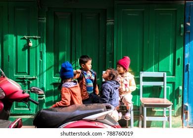 KATHMANDU, NEPAL - December 15, 2017 : Unidentified children are playing in front of the green door in street of Thamel, Kathmandu, Nepal.