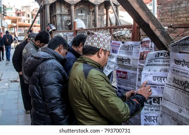 KATHMANDU, NEPAL - DECEMBER 16,2017: Nepali mens reading the newspapers beside the street.