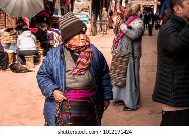 Kathmandu, Nepal - December 17, 2017 : Old Nepali lady go to pray and pay a worship at the biggest stupa in Kathmandu, Nepal.