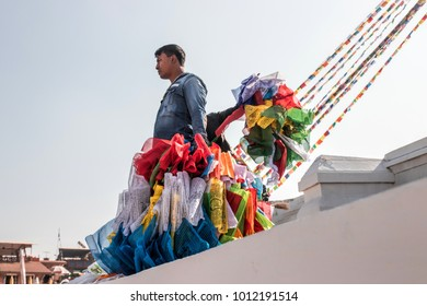 Kathmandu, Nepal - December 17, 2017 : An unidentified Napali man is carrying the prayer flags that will be decorated to the Biggest stupa in Nepal, Boudhanath.