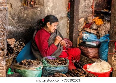KATHMANDU, NEPAL - December 24, 2017 : A female Nepali grocery shop owner in Kathmadu Dubar Square, Kathmandu city