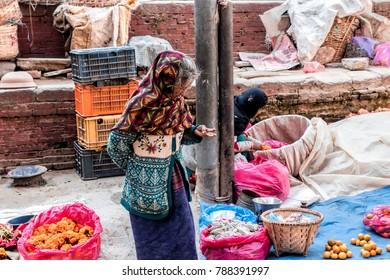 KATHMANDU, NEPAL - December 25, 2017 : Unidentified Nepali old woman standing on the street in local market of Thamel, Kathmandu, Nepal.
